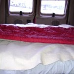 back seat turned into bed, linens, sleeping bag Photo courtesy of Ken Ilgunas