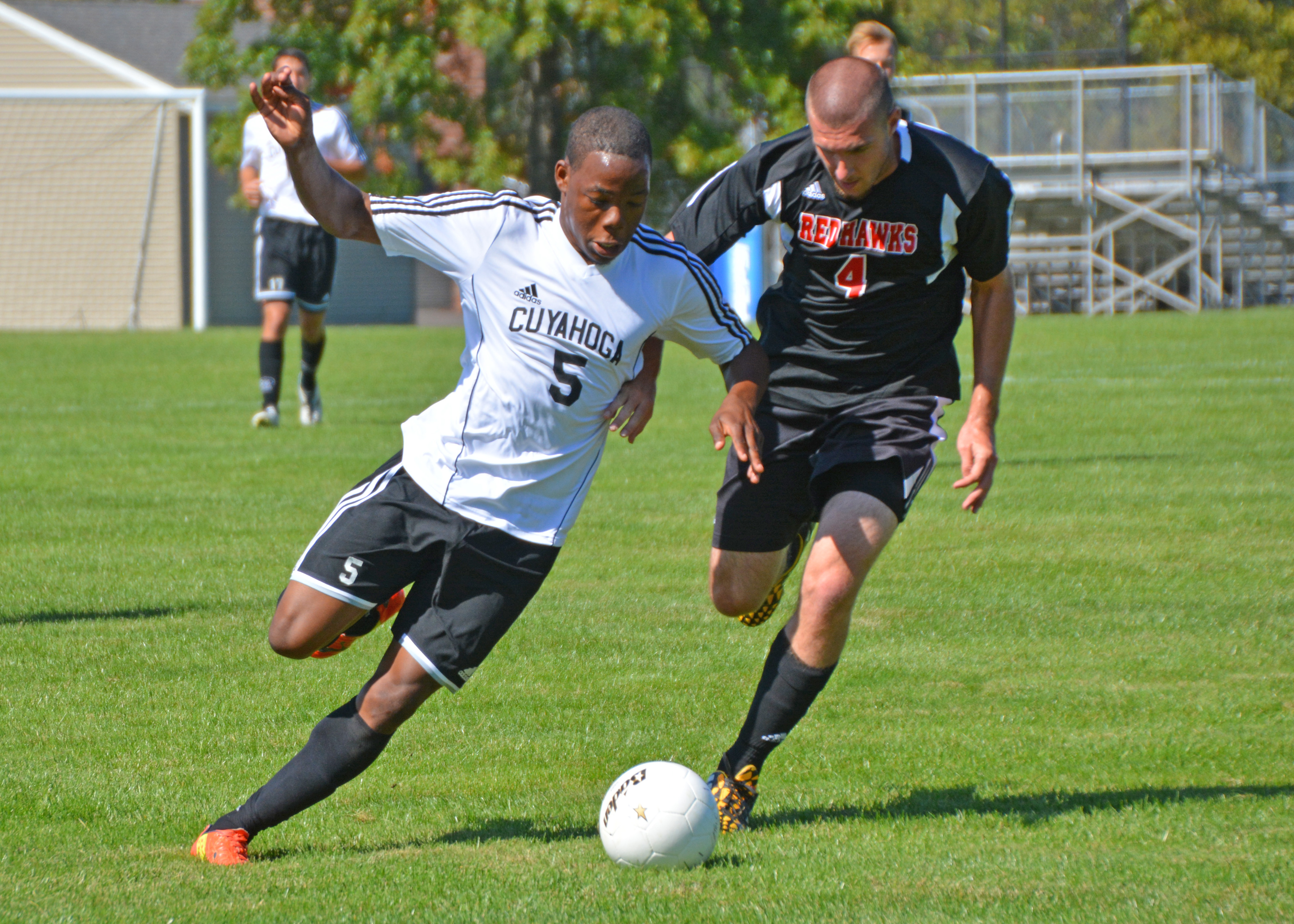 Tri-C freshman Tevin Williams drives the ball down the field with Lake Michigan College defenseman Joey Pasternak at a soccer match played at the Western Campus on Sept. 27. <i>Photo by Emily Rohm</i>